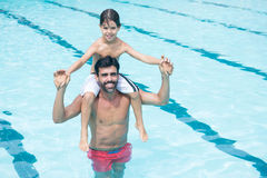 Father carrying son on shoulder in pool Royalty Free Stock Image