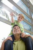 Father carrying son (8-10) on shoulders in airport, boy holding toy aeroplane, smiling, front view, low angle view (lens flare) royalty free stock photos