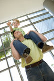 Father carrying son (8-10) on shoulders in airport, boy holding toy aeroplane, smiling, low angle view (tilt) stock images