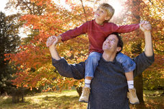 Father carrying son on shoulders in autumn Royalty Free Stock Images