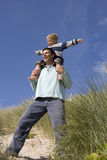Father carrying son on shoulders at beach, low angle view Stock Photography