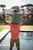 Father carrying son on shoulders near poolside. Rear view of father carrying son on shoulders near poolside Stock Images