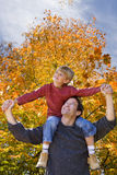 Father carrying son on shoulders outdoors in autumn Stock Photo