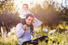 Father carrying son on shoulders, sitting on the grass Stock Photography