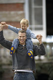 Father carrying son (3-5) on shoulders, smiling, front view, portrait Stock Photo