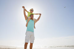 Father carrying son on shoulders on sunny beach Royalty Free Stock Photo