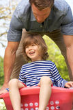 Father Carrying Son Sitting In Laundry Basket Stock Photo