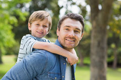 Father carrying young boy on back at park Royalty Free Stock Image