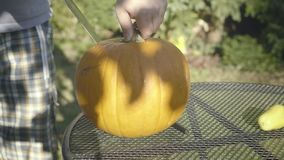 Father carves with knife Halloween creepy head. Little boy`s hands open the top of the pumpkin spooky head. stock footage