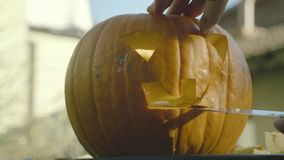 Father carves with knife Halloween creepy head. Man`s hands carve knife the pumpkin spooky mouth with teeth. stock video footage