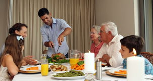 Father carving roast chicken at the dinner table Royalty Free Stock Photos
