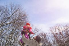 Father catch daughter on sky winter background. Girl up on hands of men playing and flying at winter forest. Father catch daughter on sky winter background Royalty Free Stock Photography