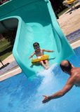 Father catches child on water slide Stock Photo