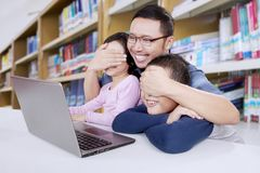 Father censoring internet contents from the kids. Father using a laptop computer censoring internet contents from his kids in a library royalty free stock image
