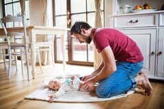 Father changing a baby girl at home. Paternity leave stock images