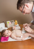 Father changing diaper of adorable baby. With a hygiene set for babies on the background Stock Photo
