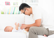 Father changing diaper and clothes for baby. Royalty Free Stock Photo
