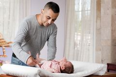 Father Changing Diaper. Father is changing diaper of her daughter Royalty Free Stock Photo