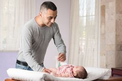 Father Changing Diaper. Father is changing diaper of her daughter Stock Image