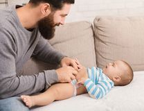 Father changing diaper to his crying baby son stock photos
