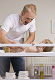 Father Changing Diapers Stock Photos