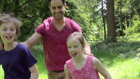 Father Chasing Children Along Woodland Path stock video footage