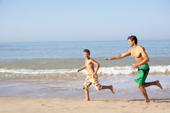 Father chasing young boy on beach Stock Photos