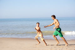 Father chasing young boy on beach. In the sun stock image