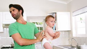 Father checking diaper of son stock footage