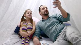 Father with cheerful little daugher playing with smartphone and talking on Skype by mobile. Father with cheerful little daugher girl playing with smartphone. Man stock footage