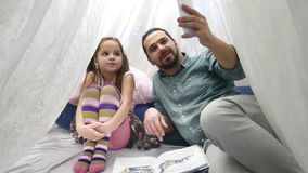 Father with cheerful little daugher playing with smartphone and talking on Skype by mobile stock video footage