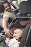 Father cheering baby up while in the car. A Father cheering baby up while in the car Stock Image