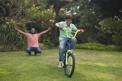 Father cheering for boy riding bicycle ri Royalty Free Stock Images