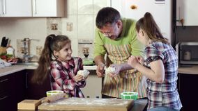 Father cheers up daughters and jaws small thick dough pieces. Funny father tries to cheer up hardworking sisters powdered with flour and jaws small thick dough stock footage