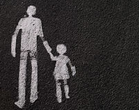 Father with child. Parental guidance - a way for pedestrians sign on asphalt Royalty Free Stock Photography