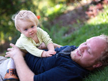Father with child. Father playing with child on a lawn stock images