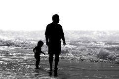 Father & Child. A father and his child strolling together on the beach Stock Images
