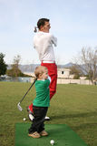 Father & Child. Young boy and his father practising on the driving range.  Focus intended for the child's face Royalty Free Stock Photography