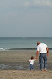 Father & Child. A father and child walking along the beach with jeans and T shirts from the back stock photo