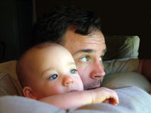 Father and Child. A father and his child rest their chins on a pillow and look out the window Stock Image