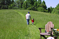 Father and Child. A father and his daughter walking together in a beautiful field Royalty Free Stock Images