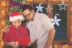Father and child amazed with a Christmas gift. Young father and his son looks amazed while opening a Christmas gift while standing at home Royalty Free Stock Photography