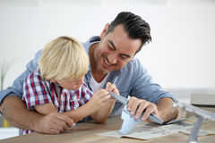 Father and child assembling a plane toy Stock Image