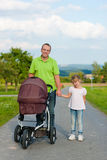 Father with child and baby buggy Stock Photography