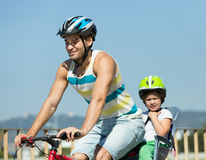 Father with child on bicycle Stock Images