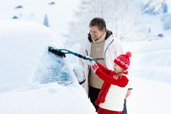 Father and child brushing off car in winter. Father and child brushing and shoveling snow off car after storm. Parent and kid with winter brush and scraper royalty free stock image