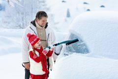Father and child brushing off car in winter. Father and child brushing and shoveling snow off car after storm. Parent and kid with winter brush and scraper royalty free stock photography