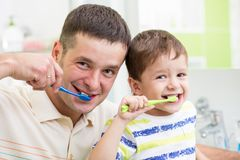 Father and child brushing teeth in bathroom. Father and his kid son brushing teeth stock images
