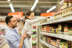 Father with child buying food at grocery store. Family, sale, shopping, consumerism and people concept - happy father with child buying food at grocery store Royalty Free Stock Photography
