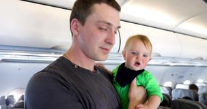 Father with the child on cabin plane. Parent on aboard holding in arms his daughter stock footage